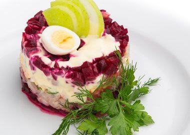 Сельдь под шубой со свеклой, яблоками, яйцом, свежим огурцом и соусом на основе йогурта